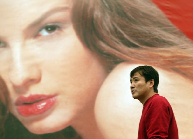 12. Китаец идет мимо плаката, рекламирующего французский спа в сердце Пекина. Китай по-прежнему остается одним из крупнейших потребительских рынков в мире. (UPI Photo/Stephen Shaver)