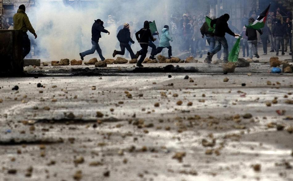 13) Палестинские демонстранты убегают от слезоточивого газа, выпущенного израильскими солдатами во время столкновений в Хевроне, 26 февраля, 2010. Премьер Палестины Салам Файяд молился в Пещере Праотцев, когда шел пятый день столкновений, несмотря на то, что Израиль собирается объявить эту и еще несколько святынь национальным наследием еврейского народа. (AFP PHOTO/DAVID FURST)