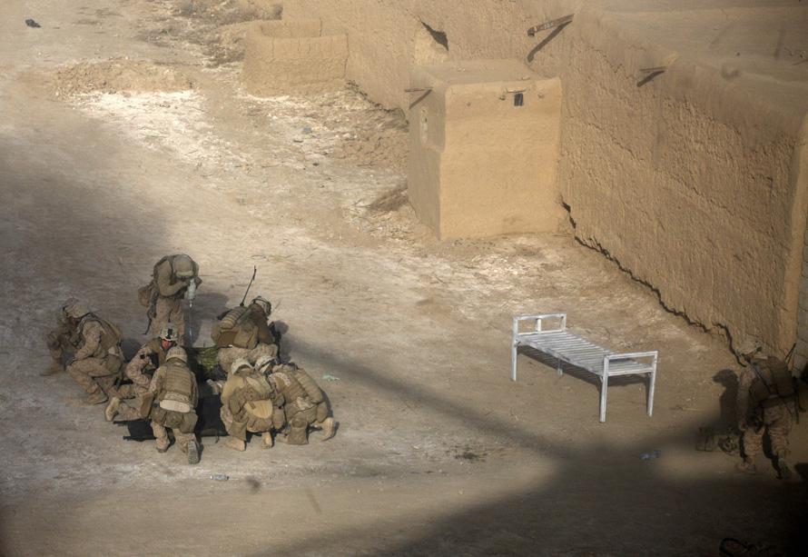 13. Солдаты прикрывают своих от пыли, поднимаемой вертолетом группы «Пегас», прилетевшим, чтобы забрать раненых, в Маржахе. Фото сделано через стекло вертолета. (AP Photo/Brennan Linsley)