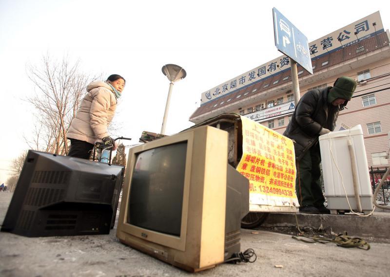 13. Китаянка выбросила старый телевизор в придорожном пункте сбора мусора в Пекине. Став крупнейшим производителем бытового мусора в мире, Китай планирует создать специальные печи для сжигания мусора, так как на обычных свалках уже нет места. (UPI Photo/Stephen Shaver)