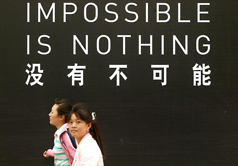 13. Китайцы проходят мимо знаменитой надписи не менее знаменитой компании. (UPI Photo/Stephen Shaver)