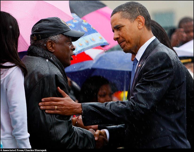 13) Под проливным дождем Барак Обама здоровается с членами семей погибших людей во время атаки 9/11.