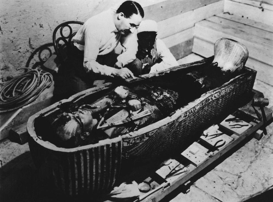 14. На этом недатированном снимке Говард Картер – археолог, открывший гробницу Тутанхамона – исследует его саркофаг. Знаменитый египетский фараон страдал волчьей пастью и косолапостью, так что он, скорее всего, ходил, опираясь на трость. (AP Photo/File)