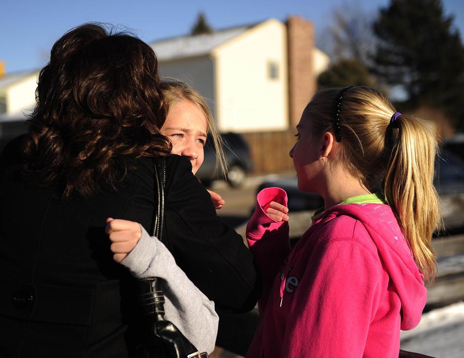 12. Перепуганные родители обнимают детей, примчавшись ан место преступления к школе «Dear Creek». (Joe Amon / The Denver Post)