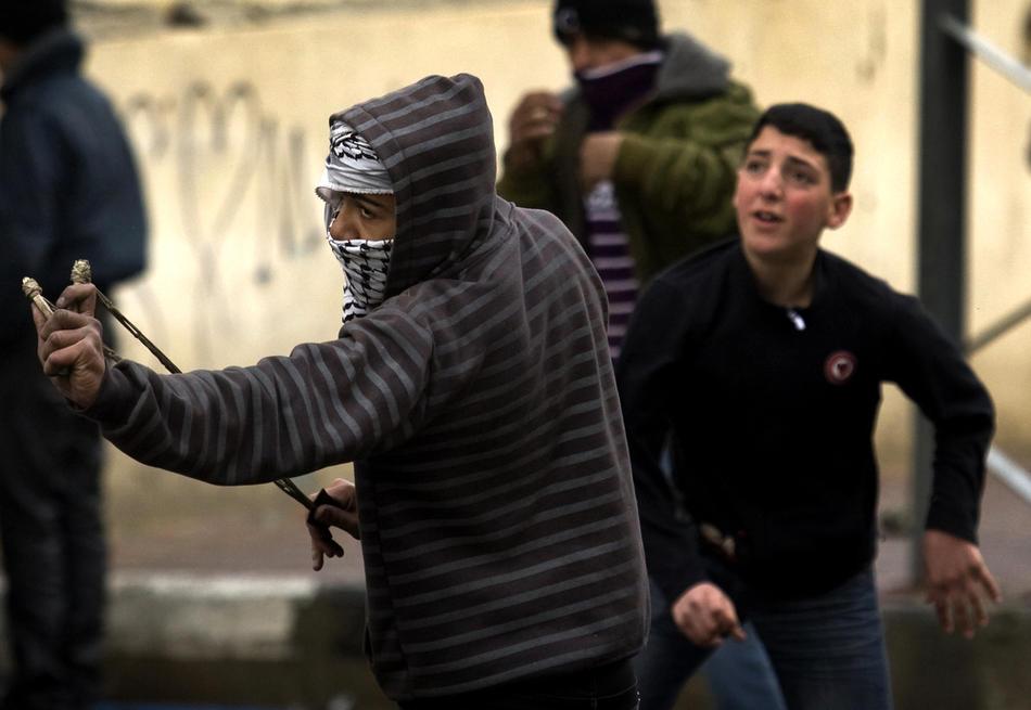 14) Палестинские участники акции протеста используют рогатки во время столкновений с израильскими солдатами в Хевроне, 26 февраля, 2010. Премьер Палестины Салам Файяд молился в Пещере Праотцев, когда шел пятый день столкновений, несмотря на то, что Израиль собирается объявить эту и еще несколько святынь национальным наследием еврейского народа. (AFP PHOTO/DAVID FURST)