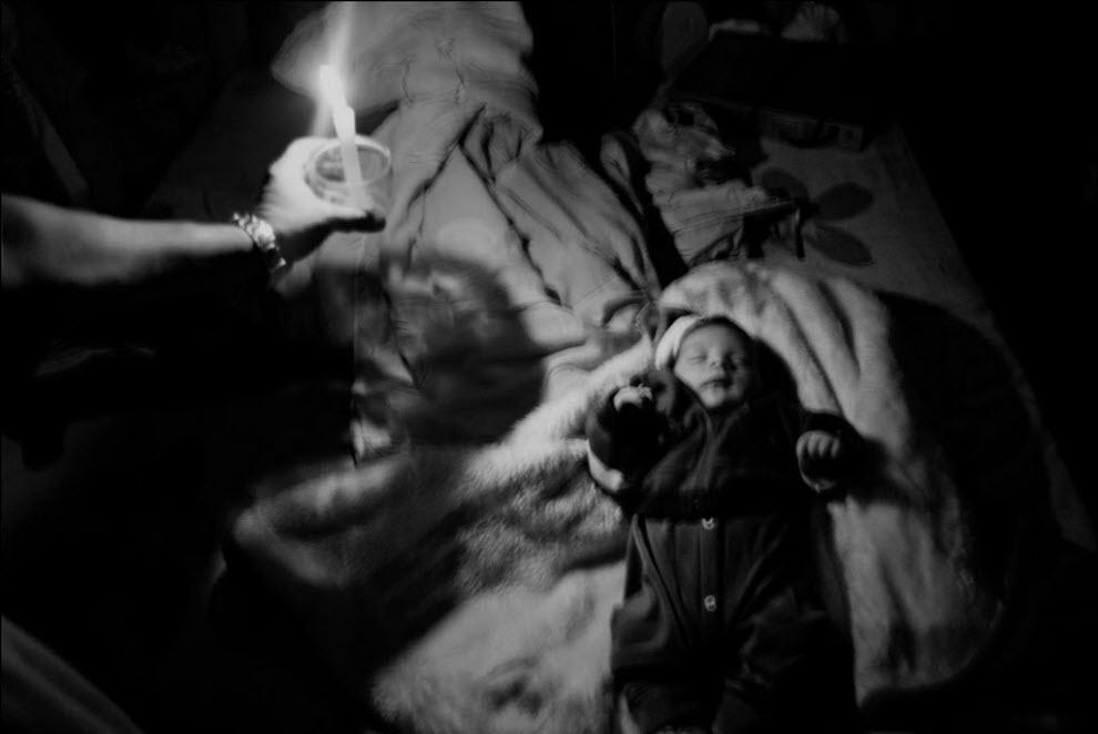 14) Арналдо Реис держит свечу рядом со своим внуком Яго Лима, он родился всего 20 дней назад. В их доме нет света, так как рабочие снесли соседние дома вместе со столбами и электрическими проводами.