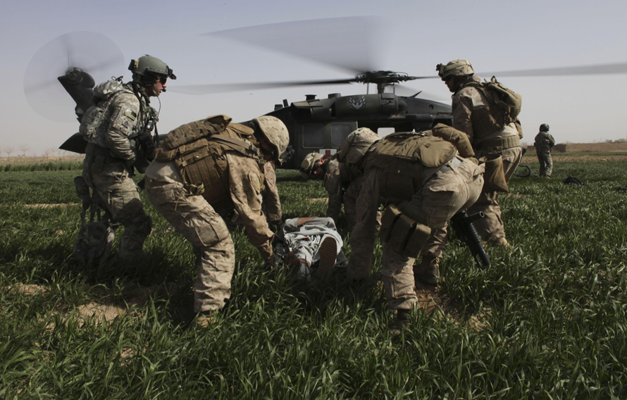 14. Солдаты несут афганца с огнестрельным ранением в вертолет в Маржахе. Слева – штабной сержант и медик Роберт Б. Коудри. (AP Photo/Brennan Linsley)