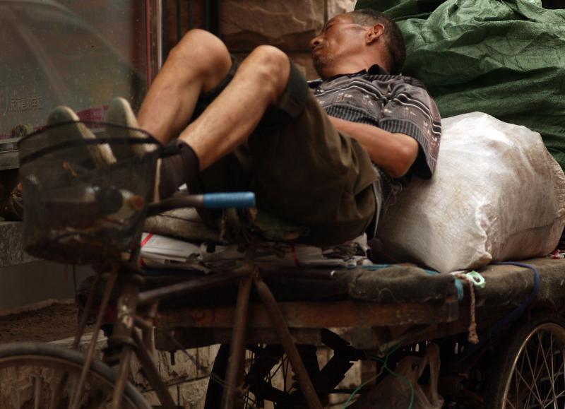 14. Китаец спит на своей тележке – обычном транспортном средстве для перевозки мусора – в Пекине. Экономика Китая поднимается своим ходом, но не достаточно быстро, чтобы справиться с безработицей без радикальных мер в политике макроэкономики. (UPI Photo/Stephen Shaver)