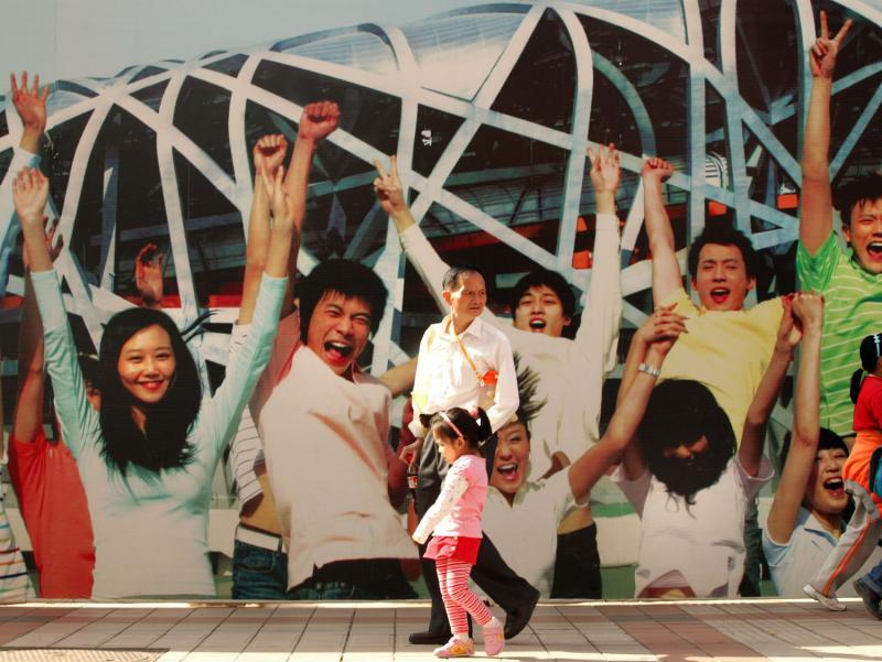 14. Китайцы проходят мимо патриотичного плаката, повешенного в преддверии Олимпийских игр в Пекине 2008 года. (UPI Photo/Stephen Shaver)