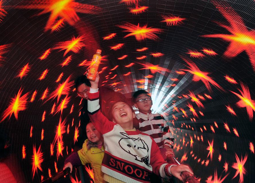 14. Дети идут по туннелю с вращающимися голографическими изображениями в научном музее во время празднования китайского нового года в Ухань, провинция Хубэй. Миллионы китайцев неделю праздновали новый год тигра. (AP Photo)