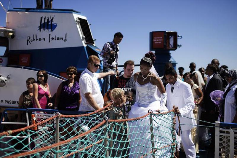 Южно-африканские молодожены спускаются с борта парома на берег острова Роббен, где находится бывшая тюрьма апардеида, в которой провел больюшую часть своего заключения Нельсон Манделла. Теперь это место стало настоящей Меккой для тех, кто хочет вступить в брак. Первая свадьба на острове Роббен состоялась в 2000 году и с тех пор ежегодно тут вступают в брак около 20-ти пар. (AFP PHOTO/GIANLUIGI GUERCIA)