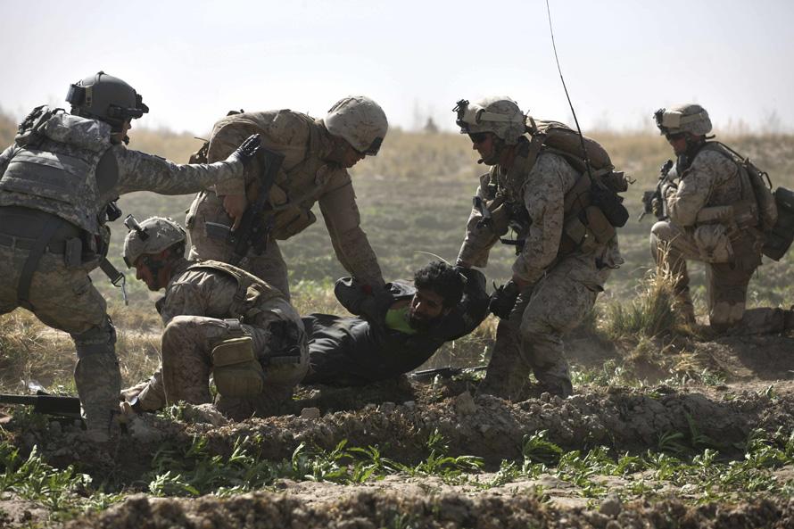 15. Штабной сержант Роберт Б. Коудри координирует действия своих людей во время внезапной перестрелки в Моржахе. На этом фото морпехи поднимают раненого талиба, подстреленного ими минутами ранее. Два раненых боевика «Талибана» были перевезены в ближайший полевой госпиталь. (AP Photo/Brennan Linsley)