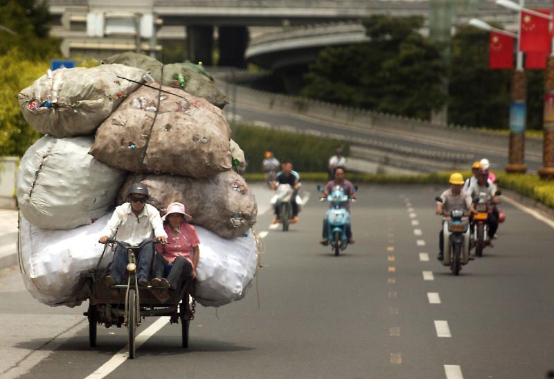 15. Китайские мусоросборщики везут мусор на свалку в Нанкине в провинции Гуанси. (UPI Photo/Stephen Shaver)
