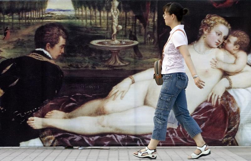 15. Китаянка проходит мимо рекламы выставки французских художников в местном музее в Пекине. (UPI Photo/Stephen Shaver)
