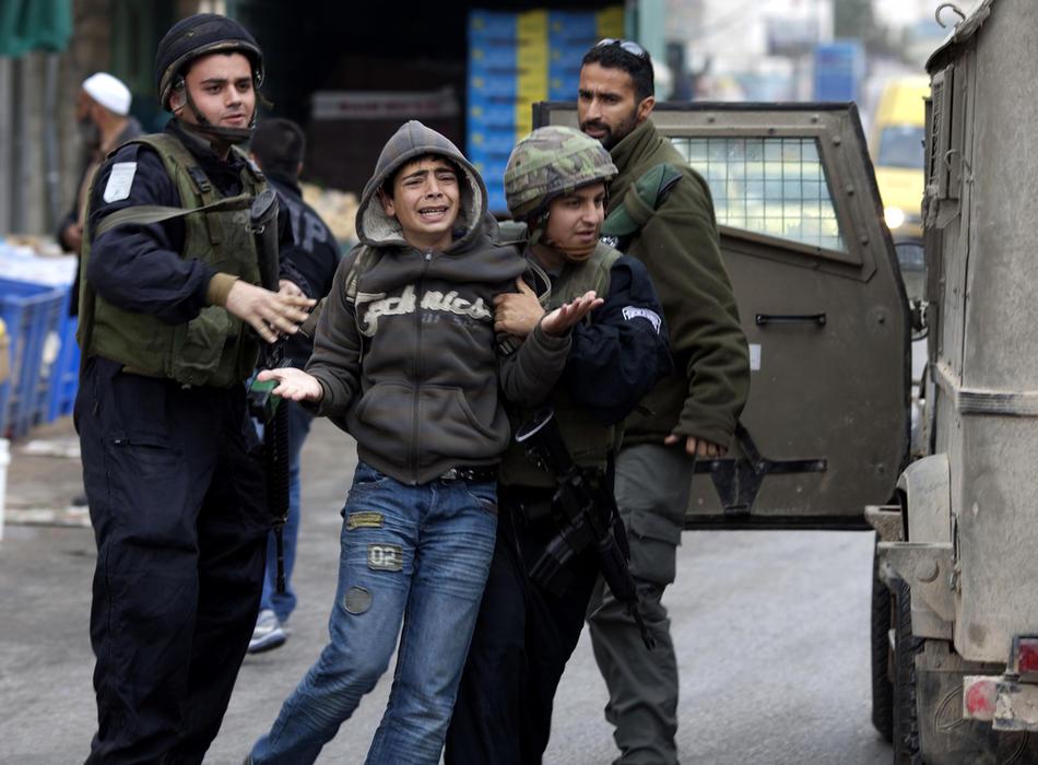 16) Израильские военные задерживают палестинского подростка, который забрасывал солдат камнями во время столкновений в Хевроне, 25 февраля, 2010. Около 100 палестинских демонстрантов несколько дней учиняли беспорядки в Хевроне. Это произошло после того, как президент Израиля Беньямин Нетаньяху объявил о намерениях включить Пещеру Праотцев и Гробницу праматери Рахели, расположенные на территории Палестины, включить в список национального наследия еврейского народа и произвести их реставрацию. (AFP PHOTO / MARCO LONGARI)