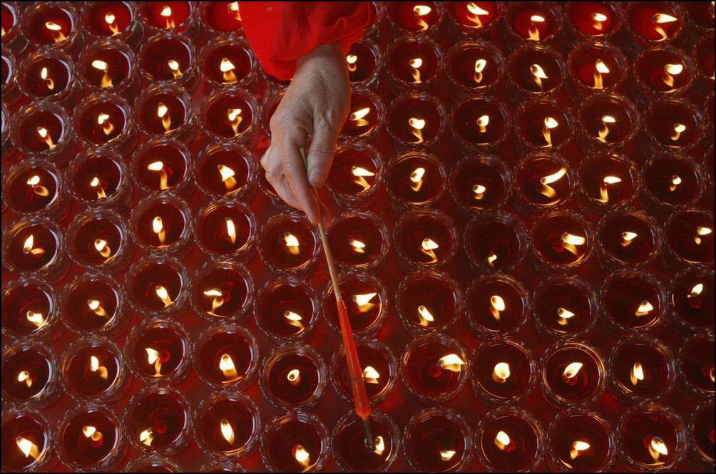 15) Женщина зажигает свечу в храме Гуан Где. (Reuters/Stringer/China)