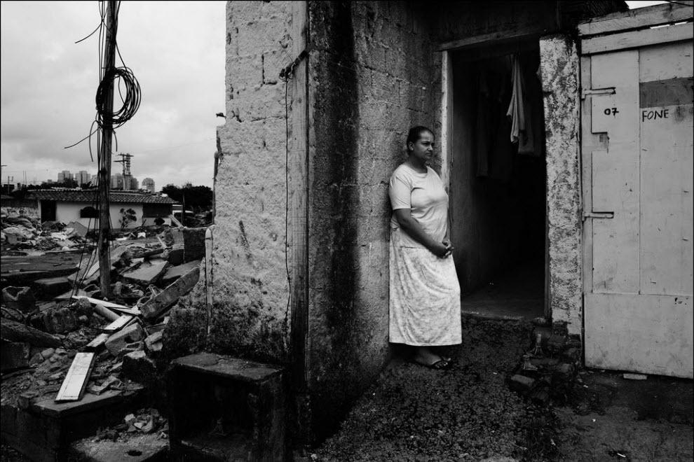 16) Сюзанна дош Сантош, стоит перед своим домом в фавеле. Ее муж зарабатывает 10 долларов в день сбором вторсырья. Сюзанна не знает куда им ехать с двумя детьми, когда снесут их дом.