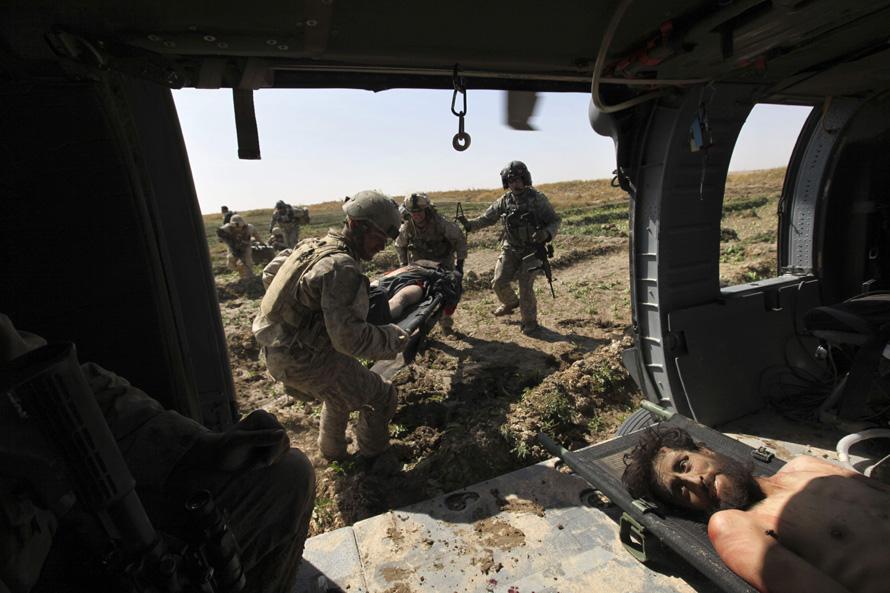 16. Оперативная группа «Пегас» спешно эвакуирует раненых (в том числе и боевиков «Талибана») на вертолет, который отвезет их в ближайший полевой госпиталь. (AP Photo/Brennan Linsley)
