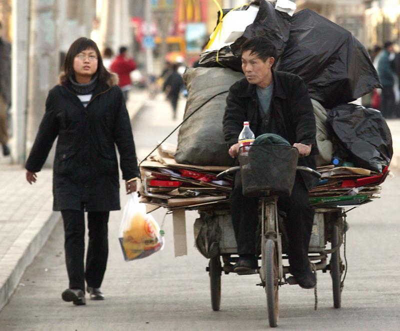 16. Китаец едет на своей трехколесной тележке, нагруженной мусором. (UPI Photo/Stephen Shaver)