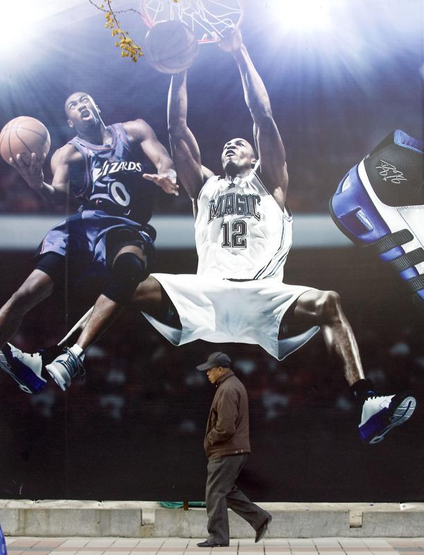 16. Китаец проходит мимо огромного плаката «Adidas» со звездами NBA, рекламирующем новую линию кроссовок, в Пекине. Китай производит 65% спортивной продукции в мире. Эта страна стала главным рынком для германского спортивного гиганта «Adidas». (UPI Photo/Stephen Shaver)