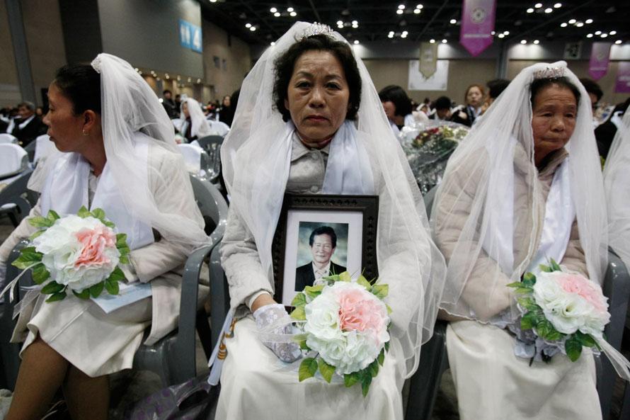 16. Невеста из Южной Кореи Ким Йонг-сун (в центре) держит портрет своего жениха Квак Юнг-шика, который не смог явиться на массовую свадебную церемонию в Гоянге. Церковь Объединения организовала массовую свадебную церемонию, в которой участвовали приблизительно 14 000 человек. (AP Photo/Ahjn Young-joon)