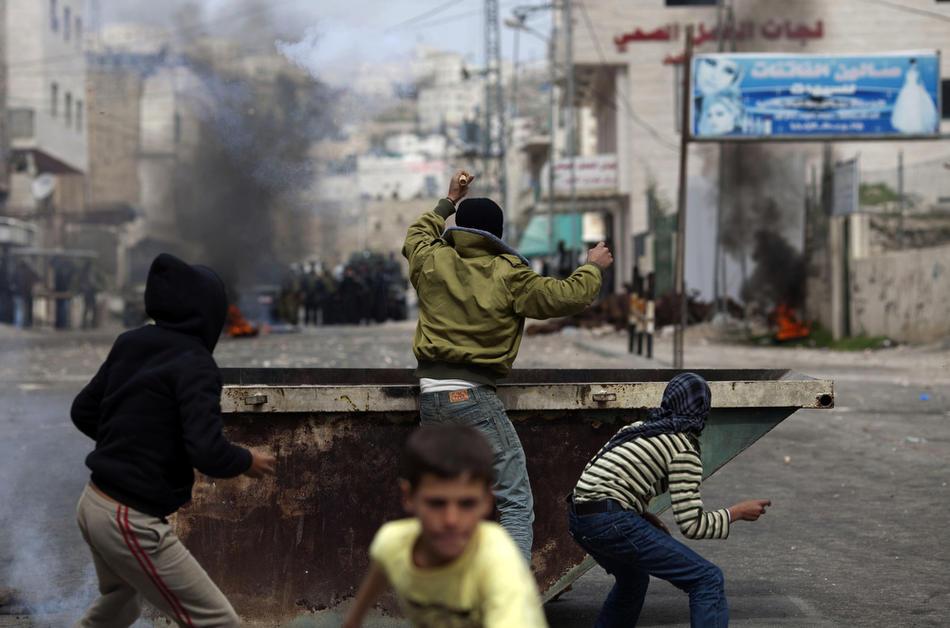 17) Палестинские мальчишки забрасывают израильские войска камнями во время столкновений с Хевроне, 25 февраля, 2010. Около 100 палестинских демонстрантов несколько дней учиняли беспорядки в Хевроне. Это произошло после того, как президент Израиля Беньямин Нетаньяху объявил о намерениях включить Пещеру Праотцев и Гробницу праматери Рахели, расположенные на территории Палестины, включить в список национального наследия еврейского народа и произвести их реставрацию. (AFP PHOTO / MARCO LONGARI)