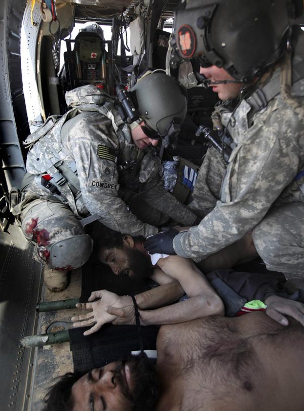 17. Штабной сержант и медик Роберт Б. Коудри (слева) и главный специалист Тимоти Джонс оказывают первую помощь связанному талибу, получившему многочисленные ранения в перестрелке. (AP Photo/Brennan Linsley)