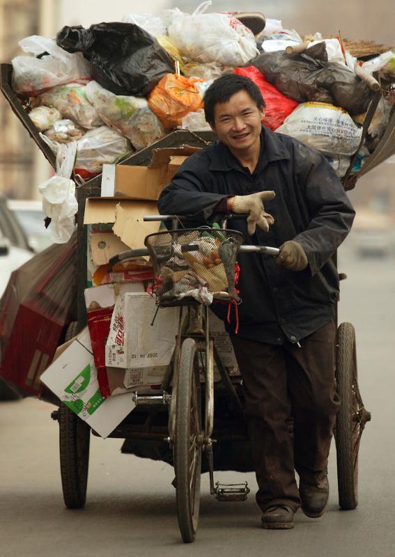 17. Китайский рабочий-мигрант обирает мусор в Пекине. (UPI Photo/Stephen Shaver)