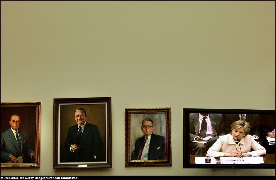 17) Госсекретарь Клинтон вещает из плазмы в окружении портретов.