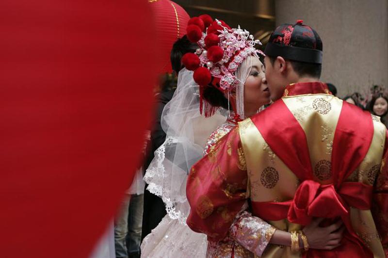Жених и невеста во время традиционной китайской свадьбы в Гонконге 14 февраля 2010. В этом году новый лунный год впервые совпал с западным праздником Дня Влюбленных. (TOPSHOTS AFP PHOTO / Dale de la Rey)