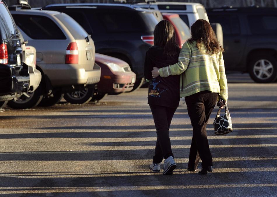 18. Родители обнимают детей, покидая территорию школы, где днем 23 февраля произошла стрельба, в результате которой были ранены два восьмиклассника. (Kathryn Scott Osler / The Denver Post)