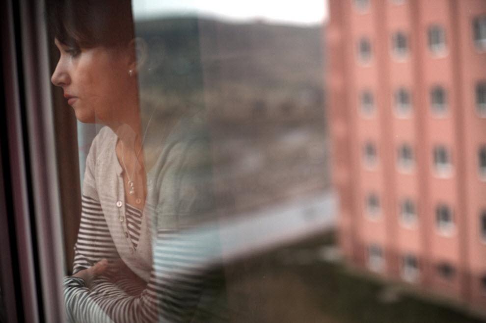 18. 28-летняя Яс Ноураккан выглядывает в окно, где вдалеке взрывают