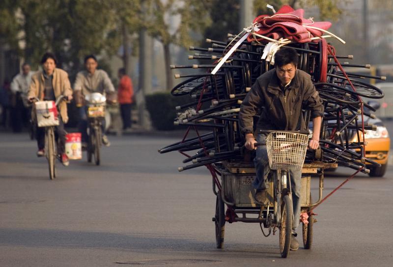 18. Китаец едет на своей тележке, перегруженной мусором, в Пекине. (UPI Photo/Stephen Shaver)