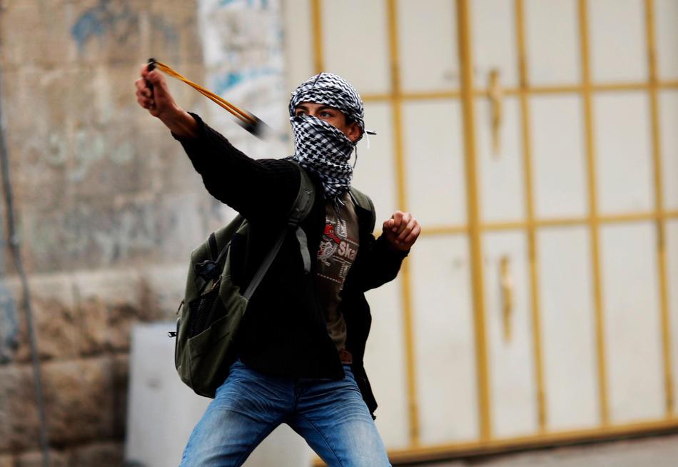 19) Палестинская молодежь использует рогатки, чтобы забрасывать израильских солдат камнями во время столкновений в Хевроне, 25 февраля, 2010. Беспорядки в Хевроне продолжаются с четверга, именно тогда Израиль объявил, что несколько святынь, расположенных на территории Палестины, будут включены в список национального наследия еврейского народа. Немногим ранее президент Палестины Махмуд Аббас предупреждал, что за таким решением может последовать «религиозная война». (AP Photo/Ariel Schalit)