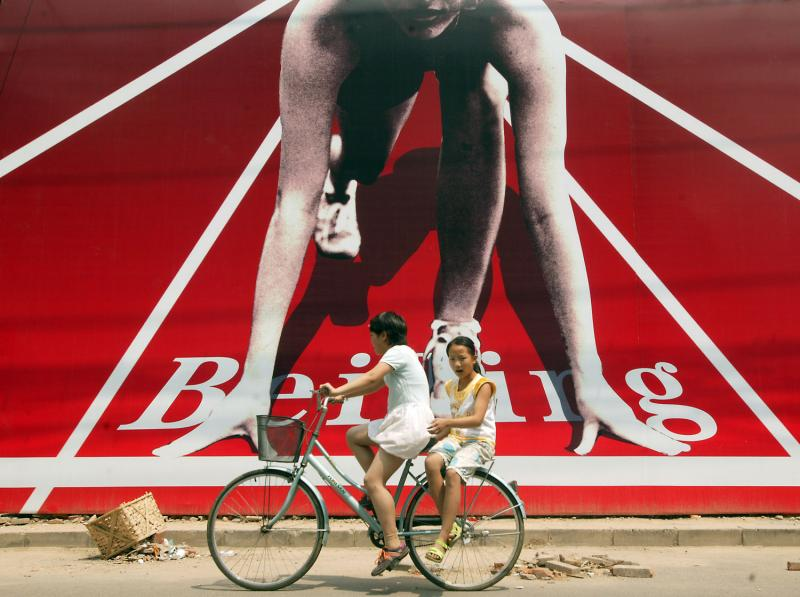 19. Две подружки проезжают мимо одного из многих огромных плакатов с тематикой Олимпийских игр в Пекине в 2008 году. (UPI Photo/Stephen Shaver)