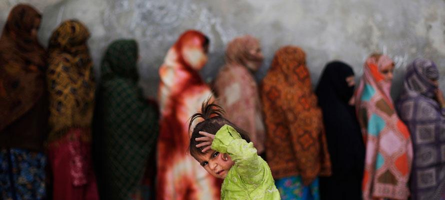 19. Пакистанская девочка ждет свою маму, которая стоит в очереди с другими женщинами, чтобы купить килограмм сахара за 54 цента в местном магазине в Исламабаде. (AP Photo/Muhammed Muheisen)