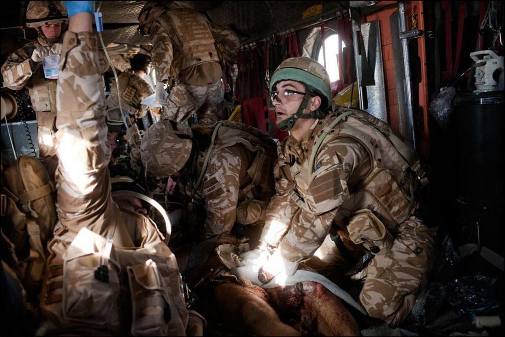 20) Солдат британской армии зажимает кровоточащие раны датского солдата, который при взрыве лишился гениталий.