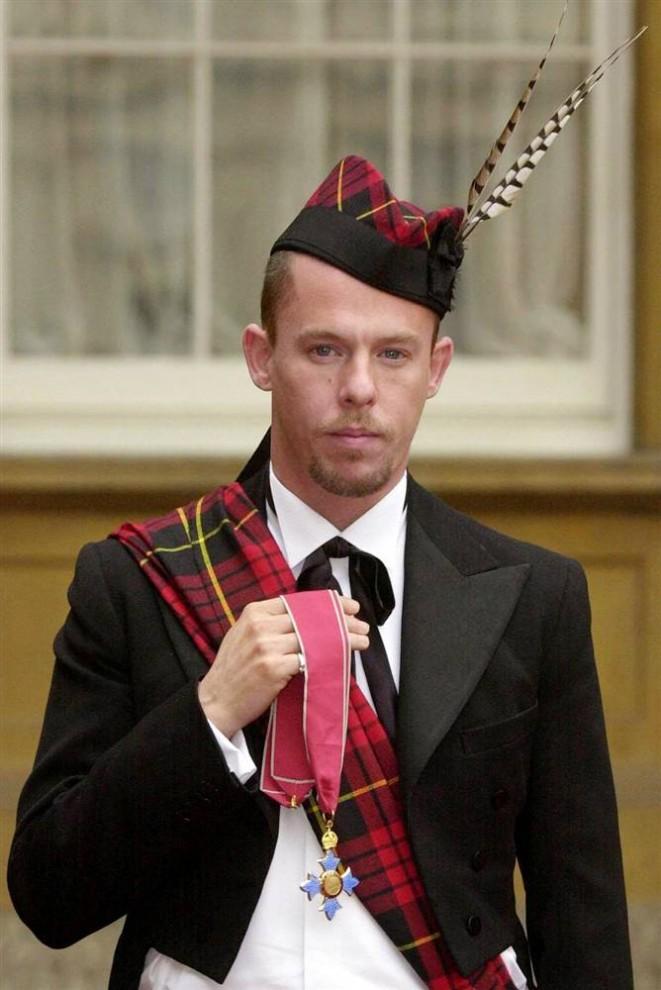 20. МакКуин позирует с орденом Британской империи, который ему вручила королева Елизавета Вторая в Букингемском дворце 29 октября 2003 года. (Matthew Fearn / Pool via AFP - Getty Images)