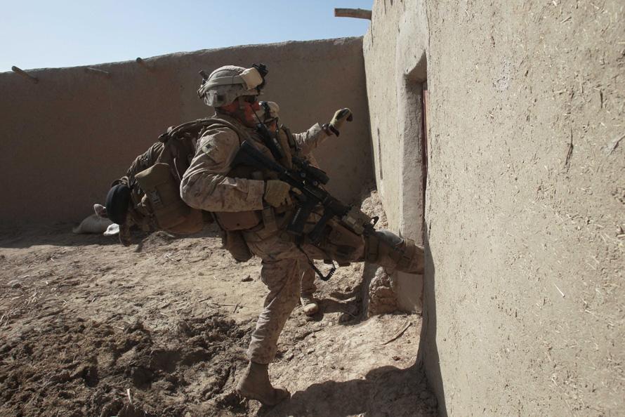 20. Кристофер Уитман открывает дверь ногой во время обыска здания на предмет обнаружения талибов. (AP Photo/David Guttenfelder)