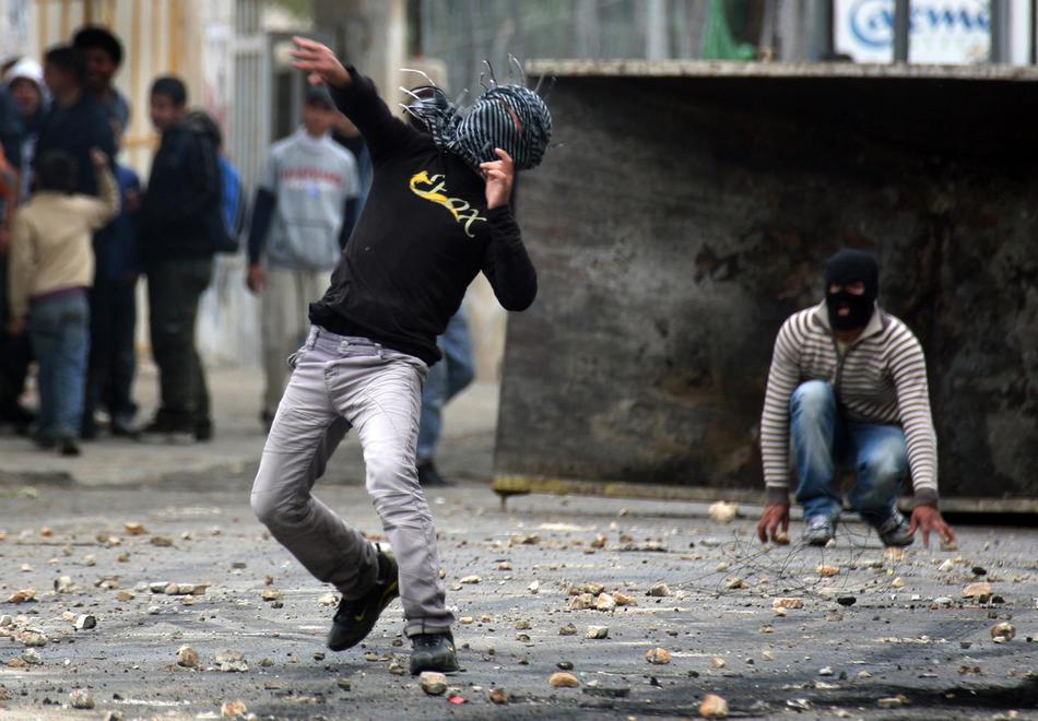 02) Палестинская молодежь забрасывает израильских солдат камнями в Хевроне, 25 февраля, 2010.  Палестинцы проводят акции протеста в Хевроне с тех пор, как 21 февраля 2010 года было объявлено, что Пещера Праотцев и Гробница праматери Рахели, расположенные на территории Палестины, будут включены в список национального наследия еврейского народа. Палестинцы возмущены действиями Израиля. ООН, США и некоторые европейские страны пытаются уладить конфликт. (Rina Castelnuovo/The New York Times)