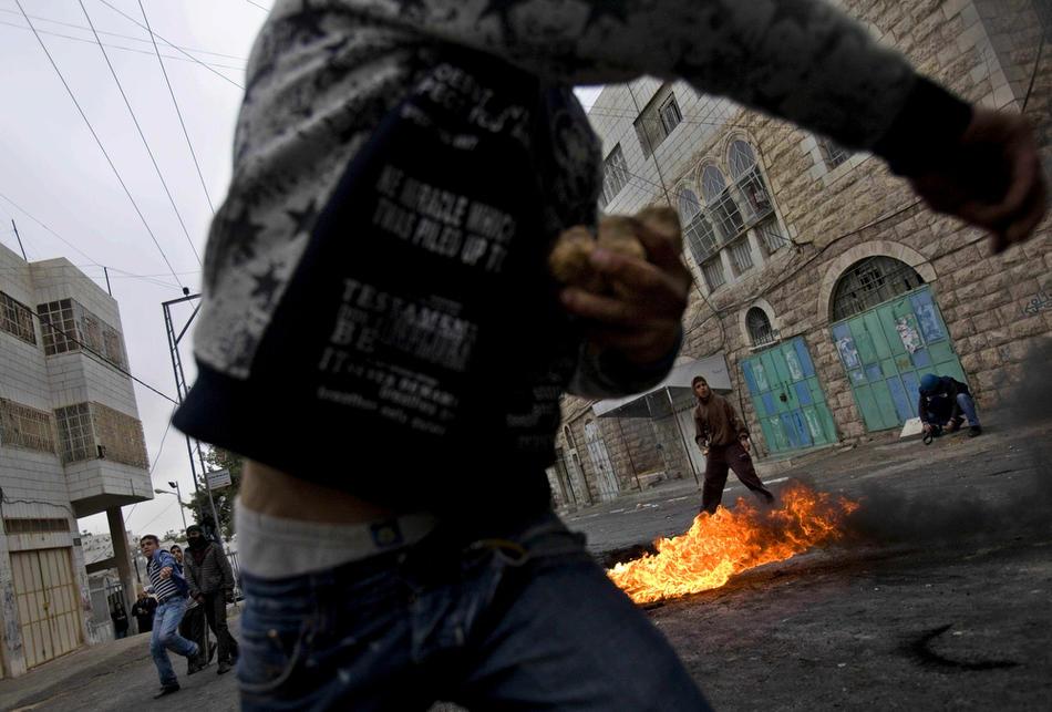 21) Палестинская молодежь закидывает израильских солдат камнями во время столкновений в Хевроне, 25 февраля, 2010. Беспорядки в Хевроне продолжаются с четверга, именно тогда Израиль объявил, что несколько святынь, расположенных на территории Палестины, будут включены в список национального наследия еврейского народа. Немногим ранее президент Палестины Махмуд Аббас предупреждал, что за таким решением может последовать «религиозная война». (AP Photo/Bernat Armangue)