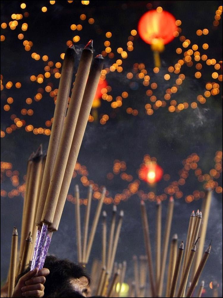 20) Люди держат курительные палочки чтобы затем опустить их в урну в храме Кван Им Тонг Худ Чо. (Reuters/Vivek Parkash)