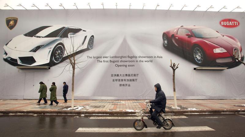 21. Мотоциклист проезжает мимо плаката с «Ламборджини» и «Бугатти» в Пекине. (UPI Photo/Stephen Shaver)