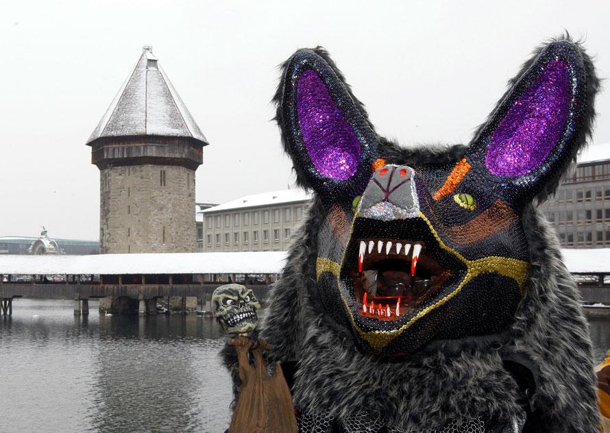 21. Участник карнавала в маске празднует на улицах Люцерна. (AP Photo/Keystone/Sigi Tischler)