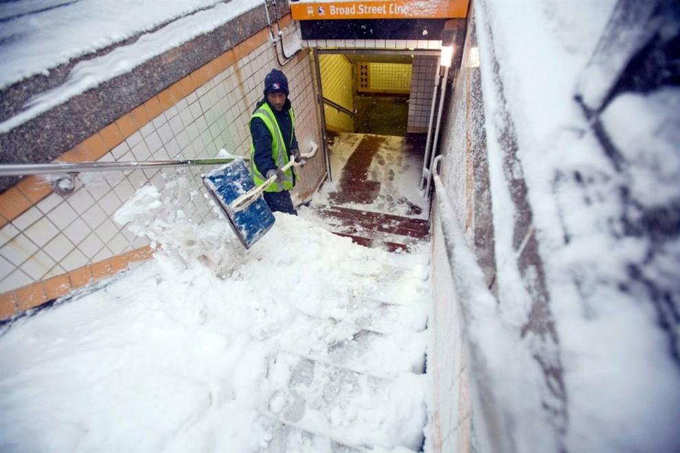 22. Работник транспортного узла Пенсильвании Эдвард Линдсей разгребает снег с лестницы в метро в Филадельфии 6 февраля. (Jessica Kourkounis / AP)