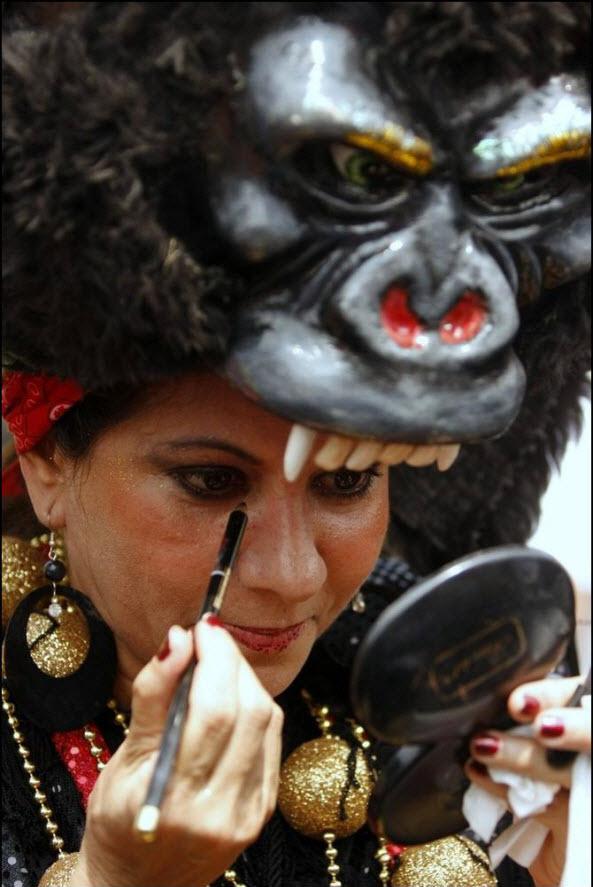 21) Женщина наносит грим перед началом карнавала.