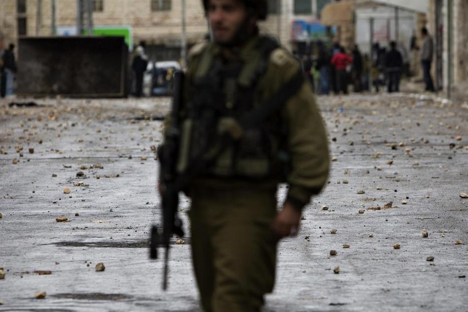 22) Израильский солдат (впереди) и палестинская протестующая молодежь (на заднем плане)  на фоне дороги, усыпанной камнями, во время беспорядков в Хевроне, 25 февраля, 2010. Беспорядки в Хевроне продолжаются с четверга, именно тогда Израиль объявил, что несколько святынь, расположенных на территории Палестины, будут включены в список национального наследия еврейского народа. Немногим ранее президент Палестины Махмуд Аббас предупреждал, что за таким решением может последовать «религиозная война». (AP Photo/Bernat Armangue)