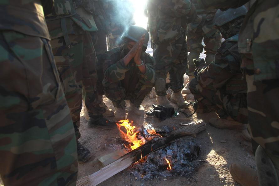 22. Солдаты афганской национальной армии греются у костра рано утром 15 февраля в Моржахе. (AP Photo/David Guttenfelder)