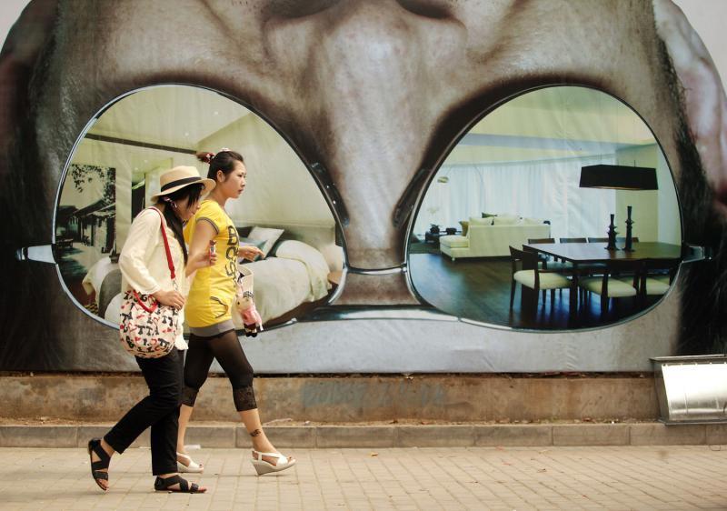 22. Две китаянки проходят мимо плаката, рекламирующего доступные квартиры, несмотря на кризис, в Пекине. В июне 2009 года цены за квартиры и дома заметно выросли. (UPI Photo/Stephen Shaver)