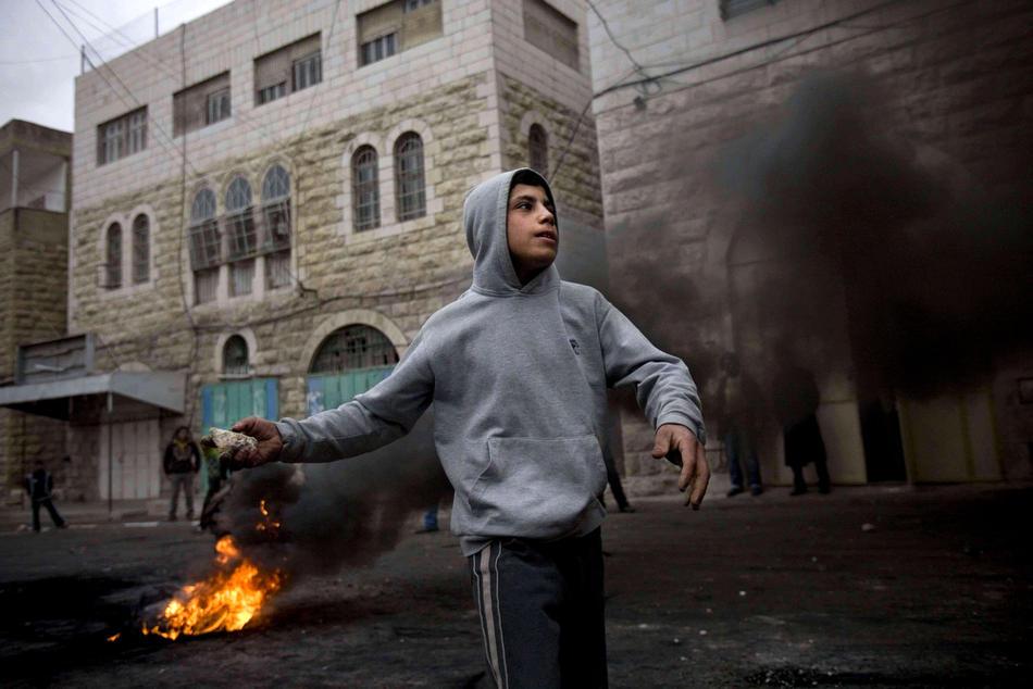 23) Палестинская молодежь закидывает израильских солдат камнями во время столкновений в Хевроне, 25 февраля, 2010. Беспорядки в Хевроне продолжаются с четверга, именно тогда Израиль объявил, что несколько святынь, расположенных на территории Палестины, будут включены в список национального наследия еврейского народа. Немногим ранее президент Палестины Махмуд Аббас предупреждал, что за таким решением может последовать «религиозная война». (AP Photo/Bernat Armangue)